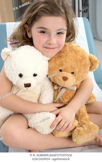 Little smiling girl holding two teddy bears in a paediatrician surgery