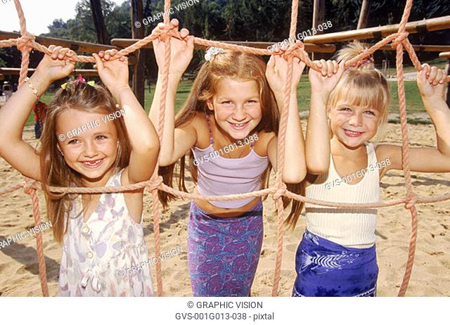 Three young girls playing on a jungle gym