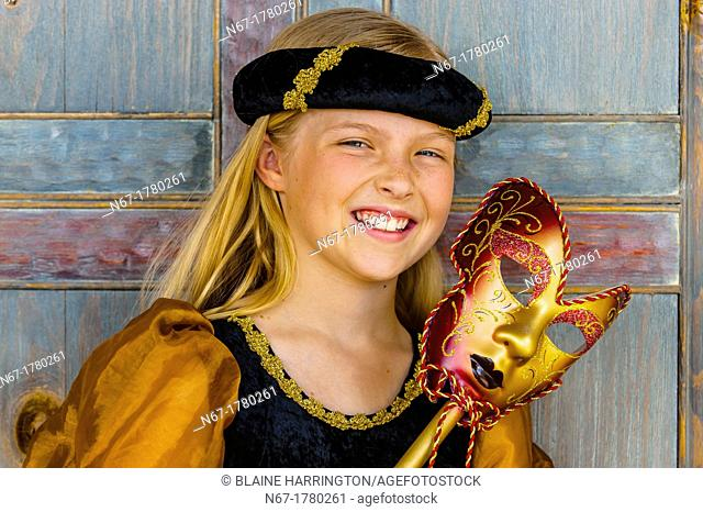 Preteen girl dressed in medieval costume and holding a Carnival mask, Cedar City, Utah USA  Cedar City is home to the Tony Award-winning Utah Shakespeare...