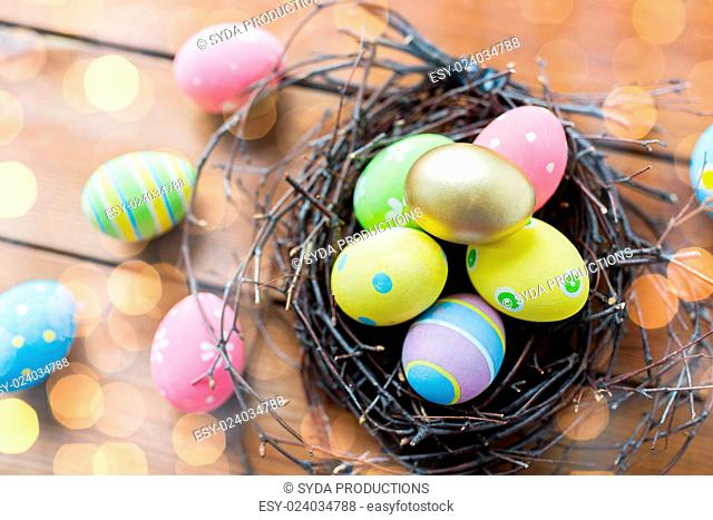 easter, holidays, tradition and object concept - close up of colored easter eggs in nest on wooden surface over lights