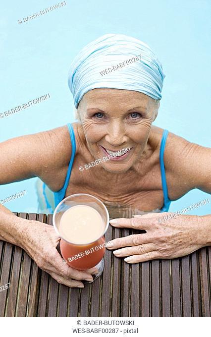 Germany, senior woman having cocktail at pool