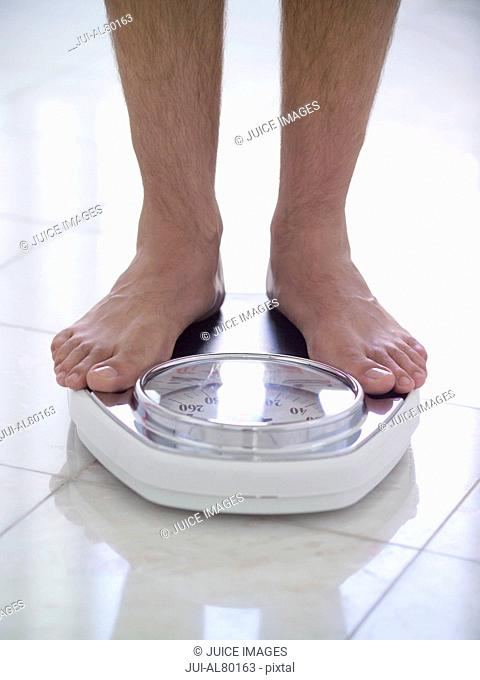 Close up of man standing on scale