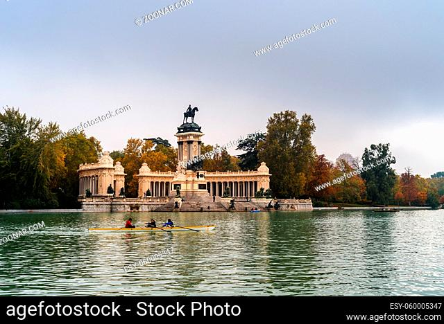 Madrid, Spain - October 24, 2020: Amateur people canoeing in the Pond of Buen Reiro Park in Madrid during Fall in the morning light a cloudy day of Autumn