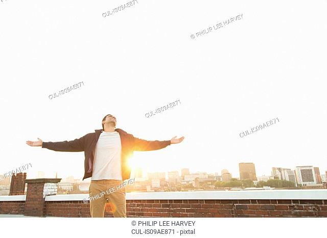 Man on rooftop with arms outstretched