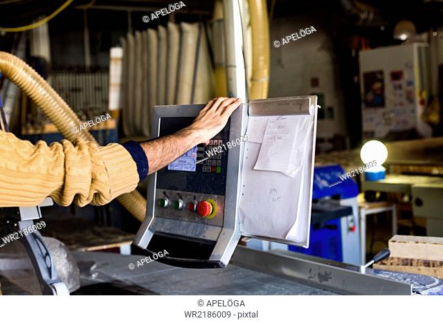 Carpenter's hand using monitor on table saw machine in workshop