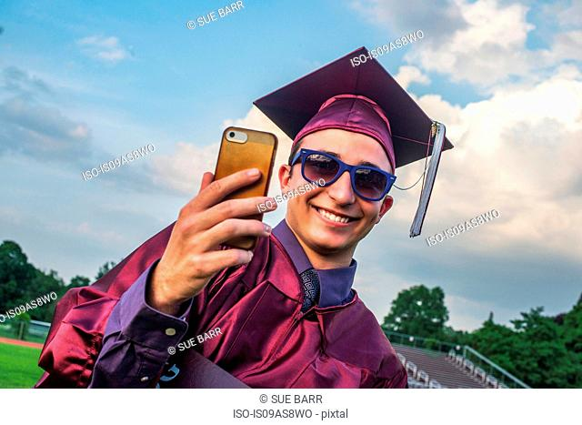 Graduate taking selfie with smartphone