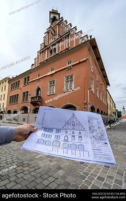 ILLUSTRATION - 15 July 2020, Bavaria, Straubing: A building plan is held in front of the burnt-out historic town hall. The city council informs itself about the...