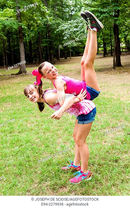2 young sisters, back to back, one lifting the other on her back