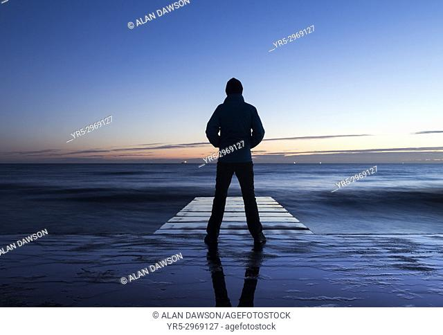 A man looks out over the North sea in pre dawn light at Seaton Carew, north east England, United Kingdom