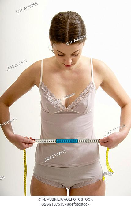 Young beautiful woman in pink underwear, measuring her waistline with a measuring tape