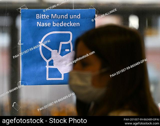 ILLUSTRATION - 07 October 2020, Rhineland-Palatinate, Mainz: A woman wearing a mouth and nose protector is standing in a bus in front of a poster saying...