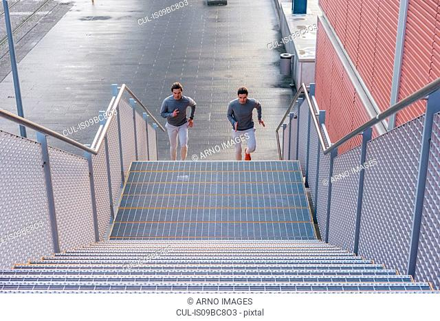 Young adult male twins running together, running up city stairway