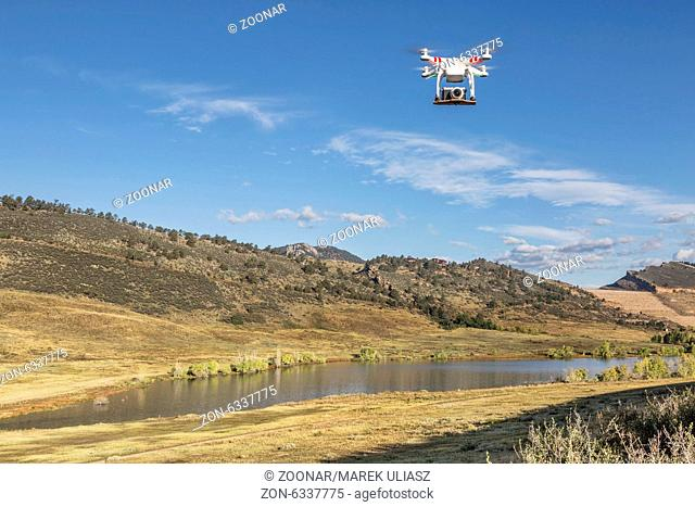a small quadcopter drone flying with a camera over a lake at Colorado foothills