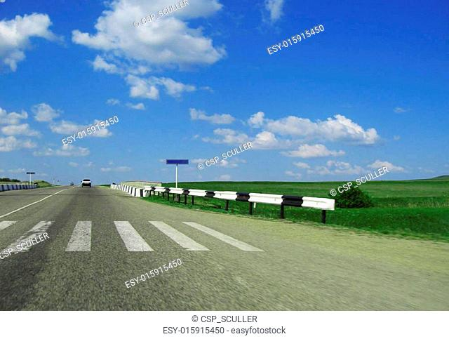 Wide highway and meadow. Clouds over and blue sky