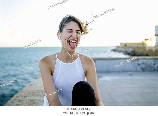 Young woman with earphones making funny faces