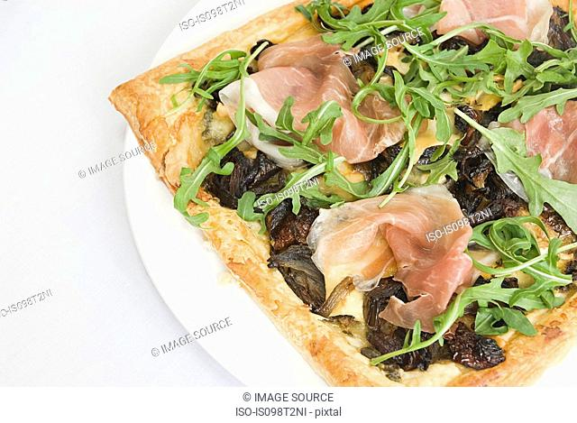 Filo pastry pizza topped with prosciutto, caramelized onion and rocket