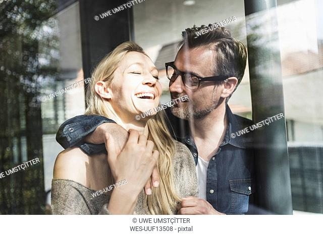Happy mature couple behind windowpane at home