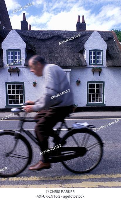 Senior man cycling in village