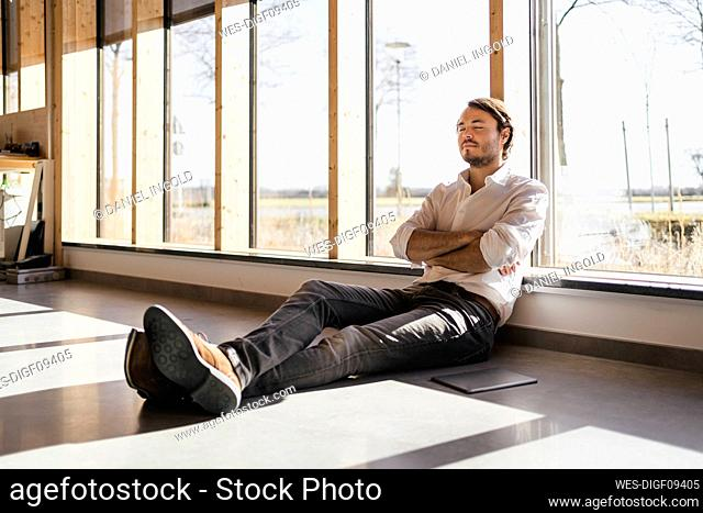 Businessman with closed eyes sitting at the window in open-plan office