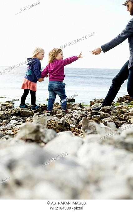 Father giving pebbles to girls at beach against sky