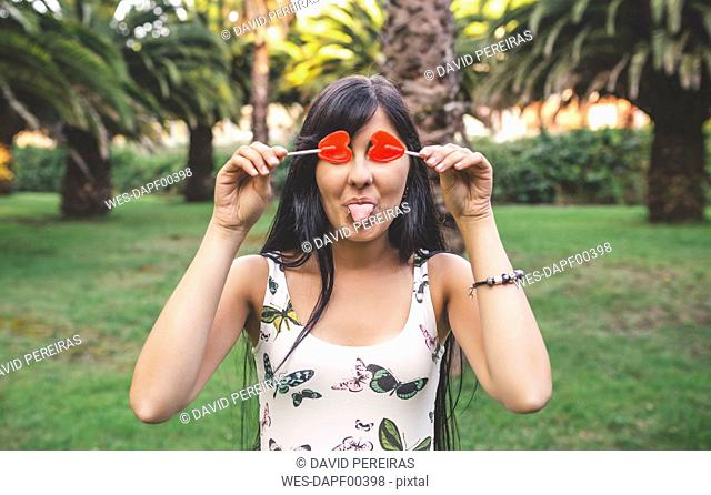 Playful young woman covering her eyes with heart-shaped lollipop