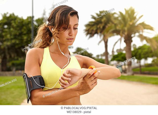 Horizontal portrait of a young runner 20-24 years old looking at smart watch