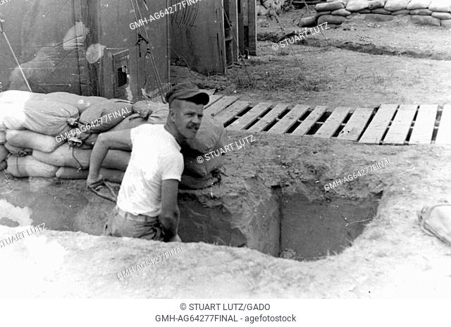 American soldier in Vietnam, wearing a white undershirt and using a shovel to dig a fox hole in front of his barracks during the Vietnam War