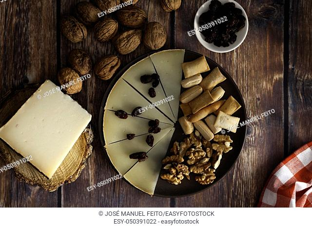Slices and piece of traditional Spanish Manchego cheese, raisins and nuts on dish on wood table and blue background from above
