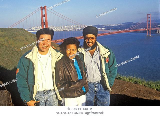 Tourists from Malaysia pose for a picture with the Golden Gate Bridge as a backdrop, San Francisco, California