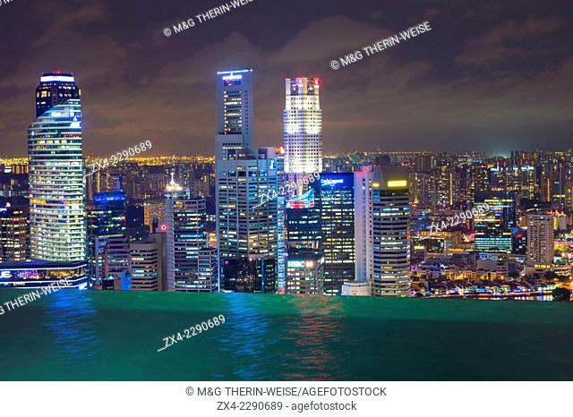 Downtown central financial district at night viewed from the Infinity pool of the Marina Bay Sands , Singapore