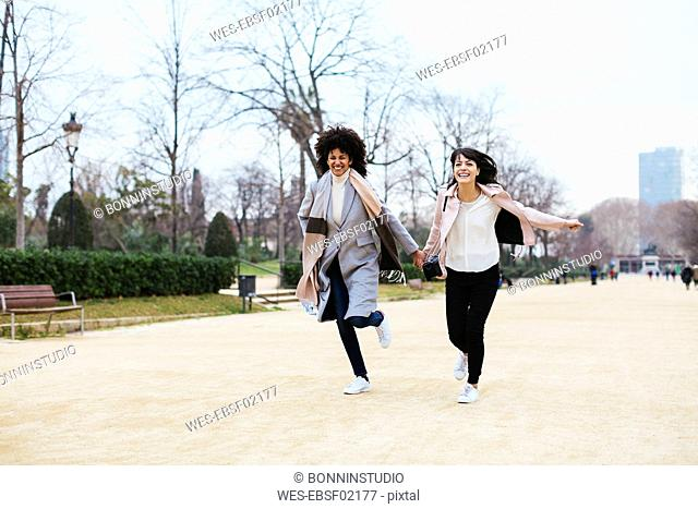 Spain, Barcelona, two exuberant women running in city park