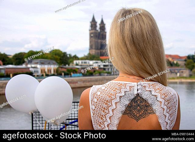 Young woman, blonde hair, looks at a diner en blanc on the cathedral in Magdeburg, wearing a tattoo on the back