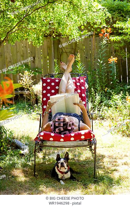 Woman with rollers in her hair reads in her garden with a Boston Terrier