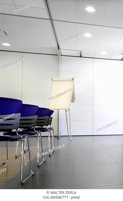 Flipchart and blue chairs in conference room