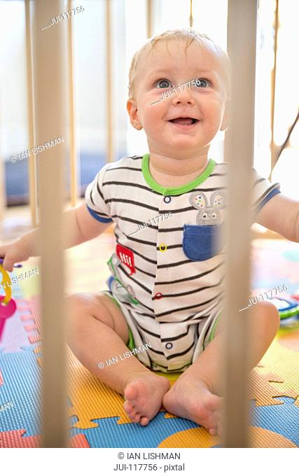 Smiling Baby Boy In Wooden Playpen At Home