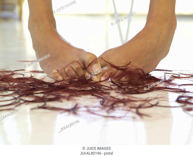 Close up of woman's bare feet next to hair clippings