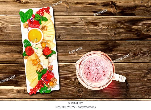 Cheese mix with berries on wooden table, top view