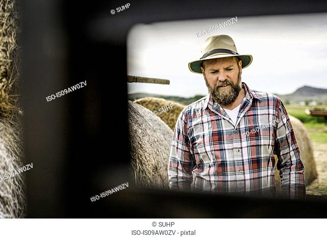 View through object of bearded mature man on farm, wearing hat looking down