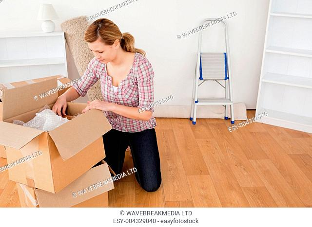 Smiling blond-haired woman preparing to move house