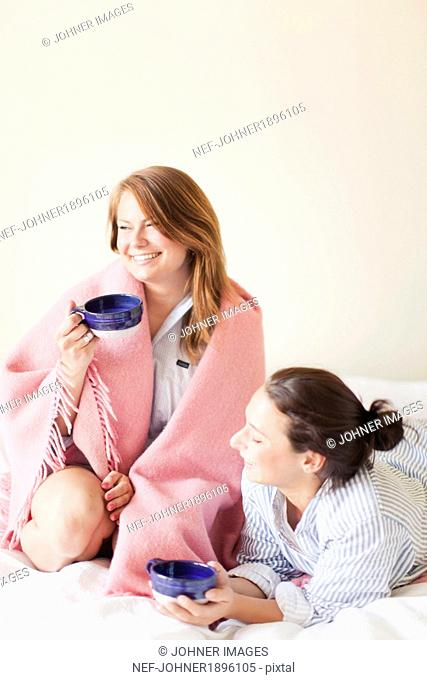 Laughing friends having coffee in bed