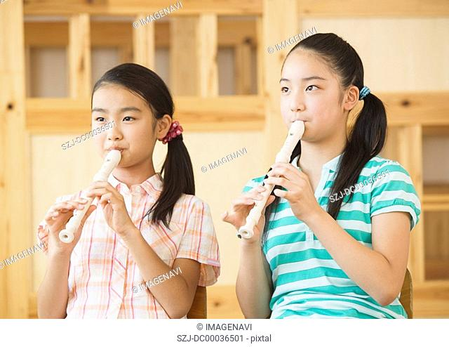 Elementary school girls playing recorders