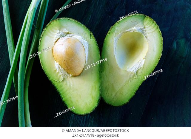 Cross section of an avocado halved with seed in tact, with a spring onion accent on greenish blue textured wooden background