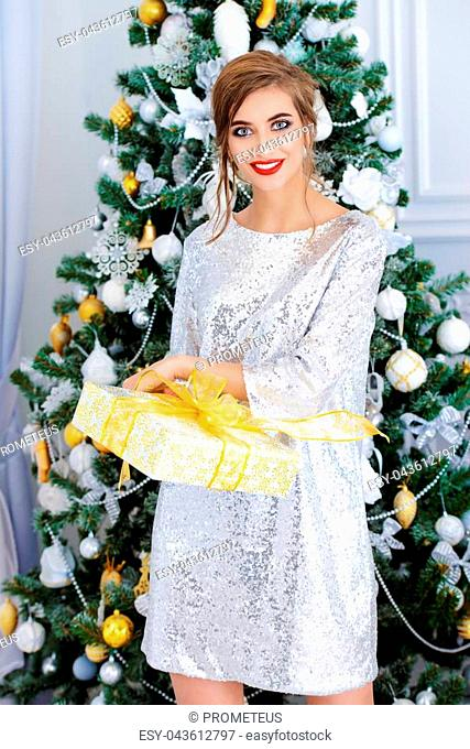 Christmas, winter holidays concept. Beautiful charming woman in evening dress holding a gift box. Luxurious apartments decorated for Christmas