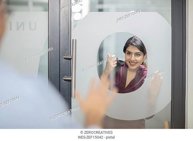 Businesswoman knocking on glass door