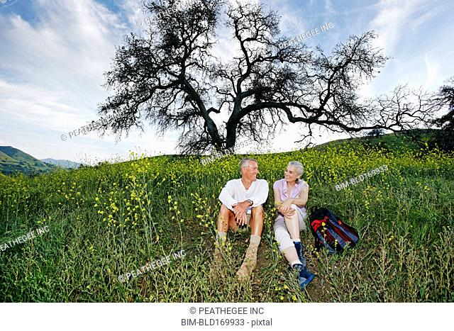 Caucasian couple sitting in tall grass
