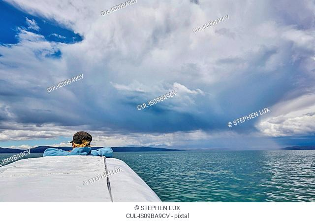 Woman on boat, looking at view, rear view, Huarina, La Paz, Bolivia, South America