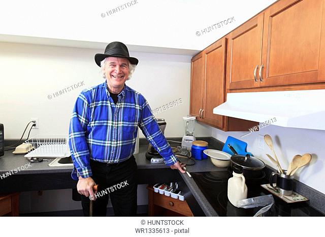 Man with Multiple Sclerosis standing in his accessible kitchen with a cane