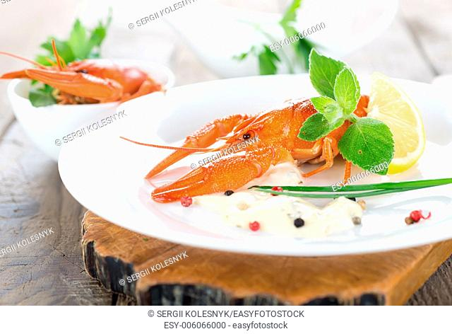 Two red lobsters with sauce, greens and lemons