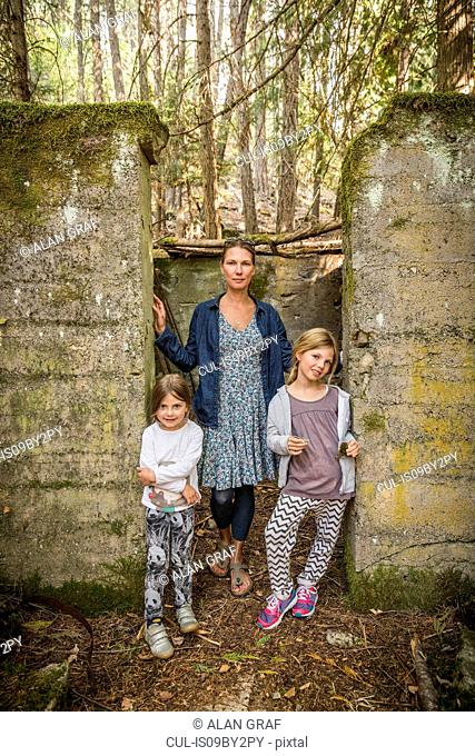 Woman and two daughters standing in derelict doorway in forest, Sandpoint, Idaho, USA