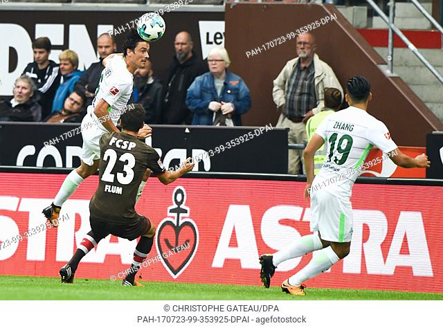 Bremen's Thomas Delaney (L) and St. Pauli's Johannes Flum (M) vie for the ball during the test match between FC St. Pauli and Werder Bremen at the Millerntor...